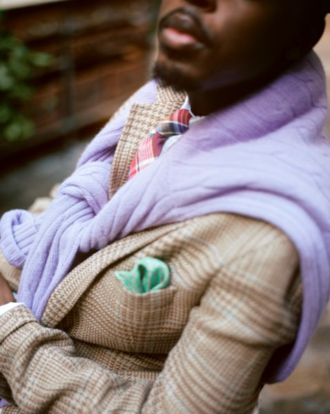 Man with light purple cable sweater draped over shoulders of jacket