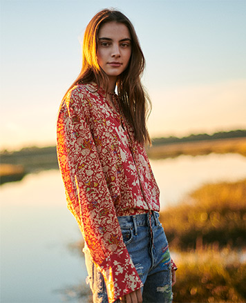 Woman in distressed jeans & floral-print red blouse