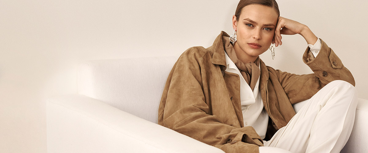 Woman in oversize tan suede jacket & white blouse & pants