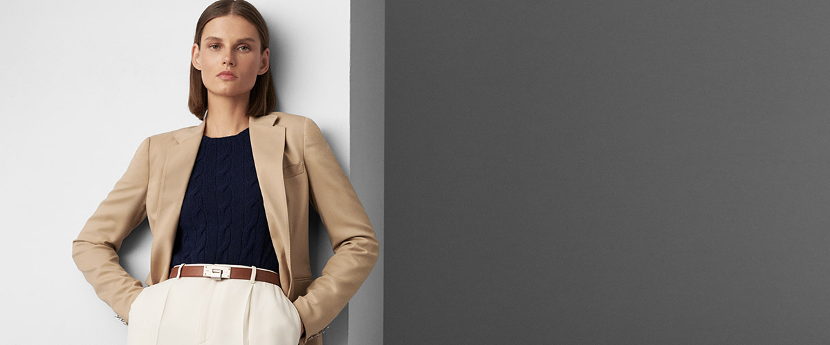 Woman in tan blazer & belted white trousers