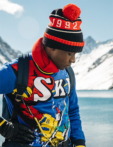 Man by lake in blue sweatshirt with bold, comic-style ski graphics