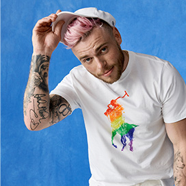 Gus Kenworthy in white tee & cap with rainbow Pony graphics