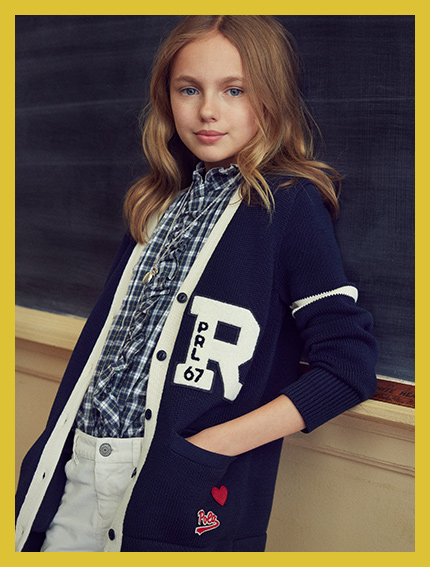 Girl in white-trimmed navy cardigan with large R graphic