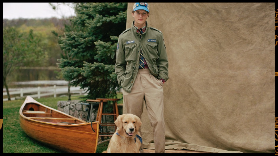 Man in green military jacket & chinos with dog by canoe